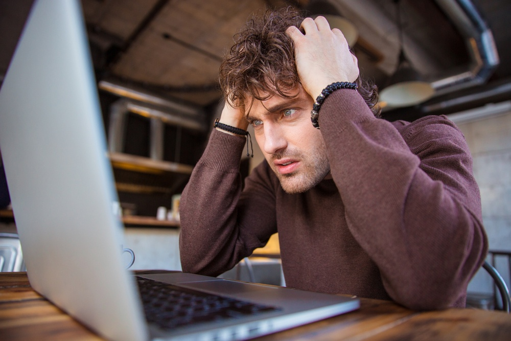 Stressful upset desperate handsome curly man in brown sweetshirt working using laptop and having headache.jpeg